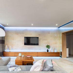 Ściana za telewizorem w salonie wykończona jest gresem w jasnym beżowym kolorze. Ten sam materiał, który zdobi ścianą znajduje się też na podłodze. Projekt: Agnieszka Morawiec. Fot. Pion Poziom Marta Behling