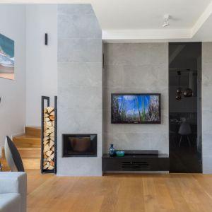 Ściana za telewizorem w salonie wykończona jest płytkimi w szarym kolorze. To super rozwiązanie do nowoczesnego salonu. Projekt: Agnieszka Morawiec. Fot. Marta Behling, Pion Poziom