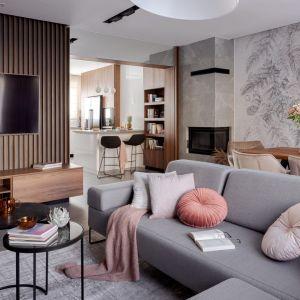 Ściana za telewizorem w salonie wykończona jest drewnianymi listewkami. Ściana wygląda bardzo efektownie. Projekt: Agnieszka Morawiec, Pracownia Projektowa Siedem. Fot. Dariusz Jarząbek Fotografia