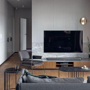 Ściana za telewizorem w salonie wykończona jest efektownym marmurem bardiglio oraz drewnianą okładziną. Projekt: Marta i Michał Raca, Raca Architekci. Fot. Tom Kurek
