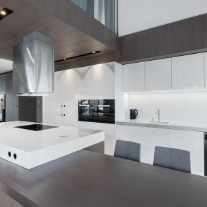 Duża kuchnia z wyspą zaaranżowana w bieli i kolorach drewna. Projekt i zdjęcie: ZAJC