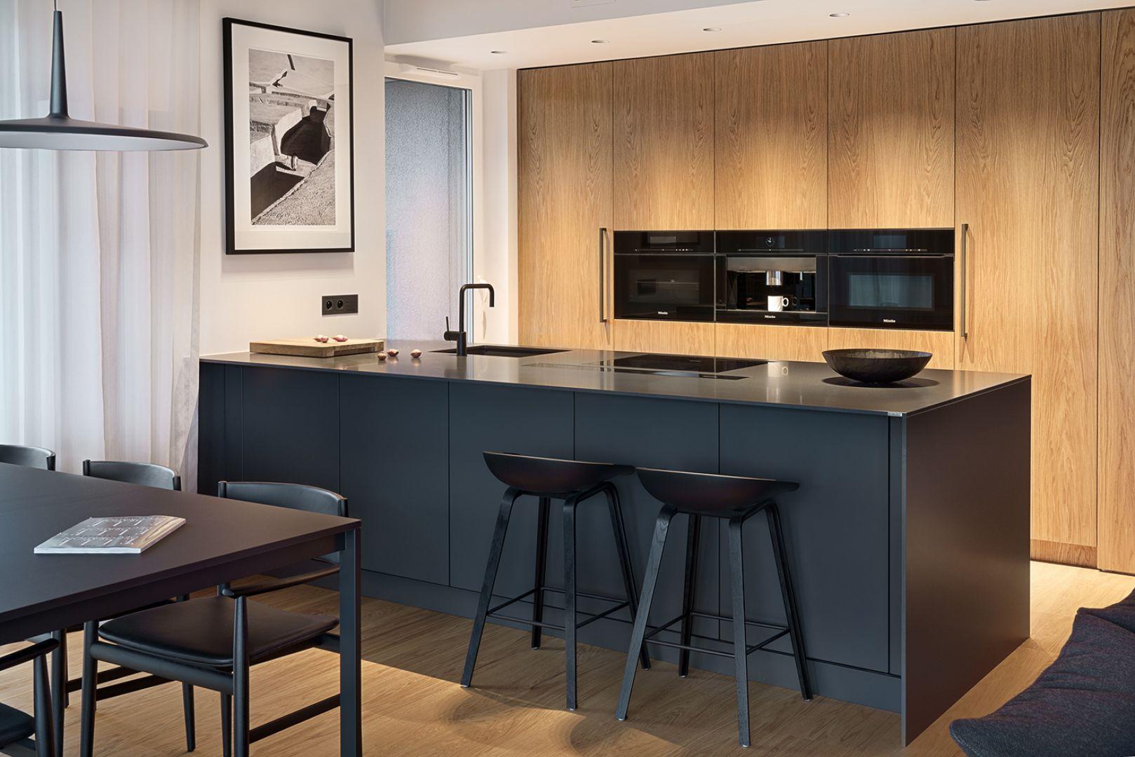 Czarna wyspa kuchenna z matowymi czarnymi frontami to świetny pomysł do kuchni w stylu loft. Projekt i zdjęcie: ZAJC