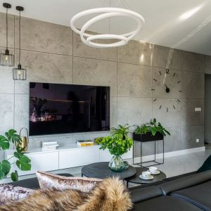 Ściana za telewizorem w salonie wykończona jest płytkami ceramicznymi w szarym kolorze. Świetnie pasują do nowoczesnego salonu. Projekt i zdjęcia: KODO Projekty i Realizacje Wnętrz