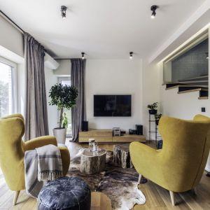 Ściana za telewizorem w salonie wykończona jest białą farbą. Ściana idealnie pasuje do drewna i do koloru. Projekt: Dominika Jurczak, DK architektura wnętrz. Fot. Krzysztof Czapor