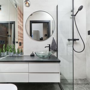Mała łazienka w bloku z wygodnym prysznicem walk-in. Przestrzeń łazienki jest optycznie powiększona, dzięki szybie prysznicowej oraz lustrom fantazyjnie rozplanowanym nad blatem umywalkowym i przy zabudowie wc. Projekt: Monika Staniec. Fot. Wojciech Dziadosz