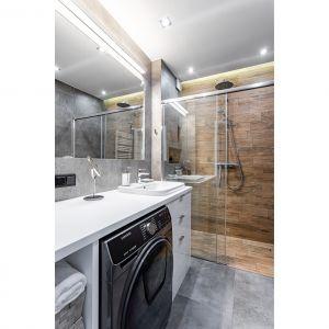 Mała łazienka w bloku z prysznicem. W łazience zastosowano płytki drewnopodobne oraz szare, imitujące beton. Projekt: Modify. Fot. Michał Młynarczyk