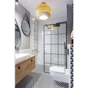 Mała łazienka w bloku z prysznicem urządzona w bieli, którą ożywiają dodatki w czarnym kolorach. Ścianka prysznicowa z czarnymi szprosami w loftowym stylu wygląda super. Projekt: Ewa Dziurska, Katarzyna Domańska, Decoroom. Fot. Marta Behling, Pion Poziom – fotografia wnętrz