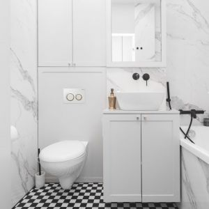 Mała łazienka w bloku z wanną urządzona w jasnych kolorach. Na ścianach i obudowie wanny położono płytki Statuario Altissimo. Doskonale imitują one przepiękne użylenia naturalnego marmuru. Projekt: Barbara Godawska z iHome Studio. Fot. Przemysław Kuciński