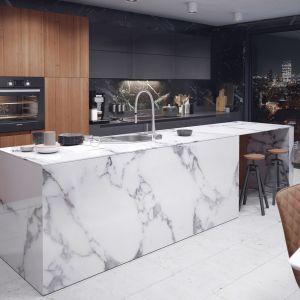 W aranżacji kuchni mocną, grafitową barwę górnych i dolnych szafek kuchennych projektant skontrastował z białym marmurem wyspy i wielką drewnianą powierzchnią zabudowy meblowej w formie szafy. Fot. Ferro