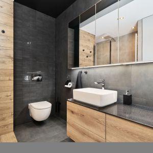 W łazience znajduje się wanna z opcją prysznica, toaleta, umywalka ustawiona na blacie oraz szafa, w której ukryta jest pralka, suszarka i miejsca na środki czystości. Projekt: Monika Staniec. Fot. Wojciech Dziadosz