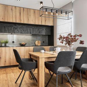 Minimalistyczne linie mebli w kuchni zbudowane są z dwóch tekstur: laminat drewniany oraz czerń z rysunkiem przecierek. Projekt: Monika Staniec. Fot. Wojciech Dziadosz
