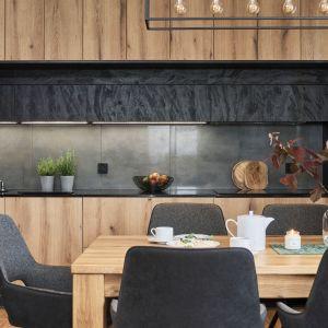 W jadalni stoi solidny, drewniany stół i kilka krzeseł, nad stołem wisi zaś geometryczna lampa. Projekt: Monika Staniec. Fot. Wojciech Dziadosz