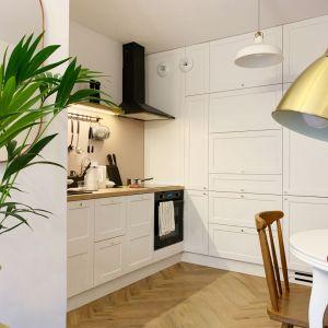 Mała kuchnia w bloku urządzona w bieli z dodatkiem drewna. Połączona jest w niedużym salonem i z jadalnią. Projekt i zdjęcia: Duch Projektanci