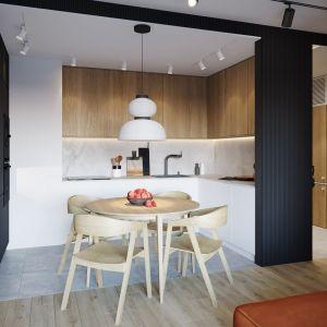 Mała kuchnia w bloku w formie aneksu z drewnianymi szafkami i ryflowaną zabudową w kolorze grafitowym. Projekt: architekt Sebastian Marach, YONO Architecture, MAST. studio - Maria Trojnara, Joanna Stawiak