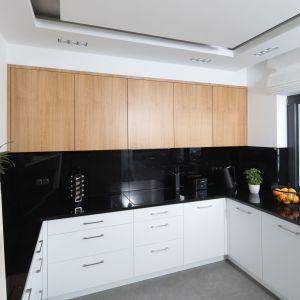Ściana nad blatem w kuchni wykończona jest szkłem w czarnym kolorze. Idealnie pasuje ono do drewna i do bieli. Projekt: Agnieszka Hajdas-Obajtek. Fot. Bartosz Jarosz