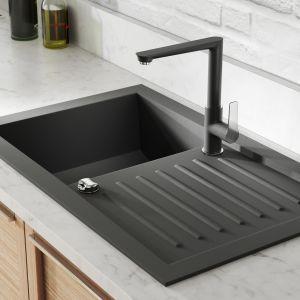Uwagę zwraca – ulokowana w ciągu zabudowy kuchennej – strefa zmywania. Stanowią ją jednokomorowy zlewozmywak w ciemnym kolorze z ociekaczem, i stojąca – także ciemna – bateria. To model Adore Black/Chrome, pokryty elegancką czarną powłoką i chromem. Fot. Ferro