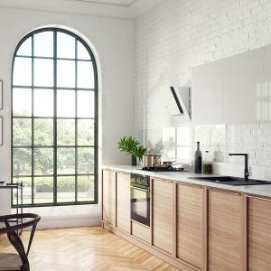W kuchennej aranżacji biel ścian i górnych półek zabudowy meblowej zestawiono z drewnianymi szafkami dolnymi i klasycznym parkietem w jodełkę. Fot. Ferro