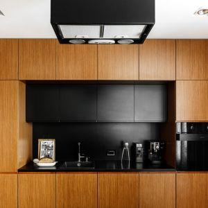 Nowoczesna kuchnia to połączenie drewna i czerni. Projekt: pracownia Magma. Fot. Fotomohito