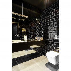 Czarna bryła mieszcząca umywalkę jest jednocześnie pojemną szafką na ręczniki i kosmetyki. Projekt: pracownia Magma. Fot. Fotomohito