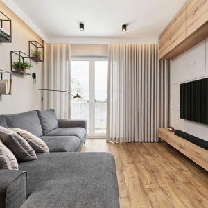 Mały salon w bloku urządzony w jasnych kolorach. Ścianą za telewizorem wykończona jest płytami z betonu, na podłodze mamy panele winylowe. Projekt: Monika Staniec. Fot. Wojciech Dziadosz
