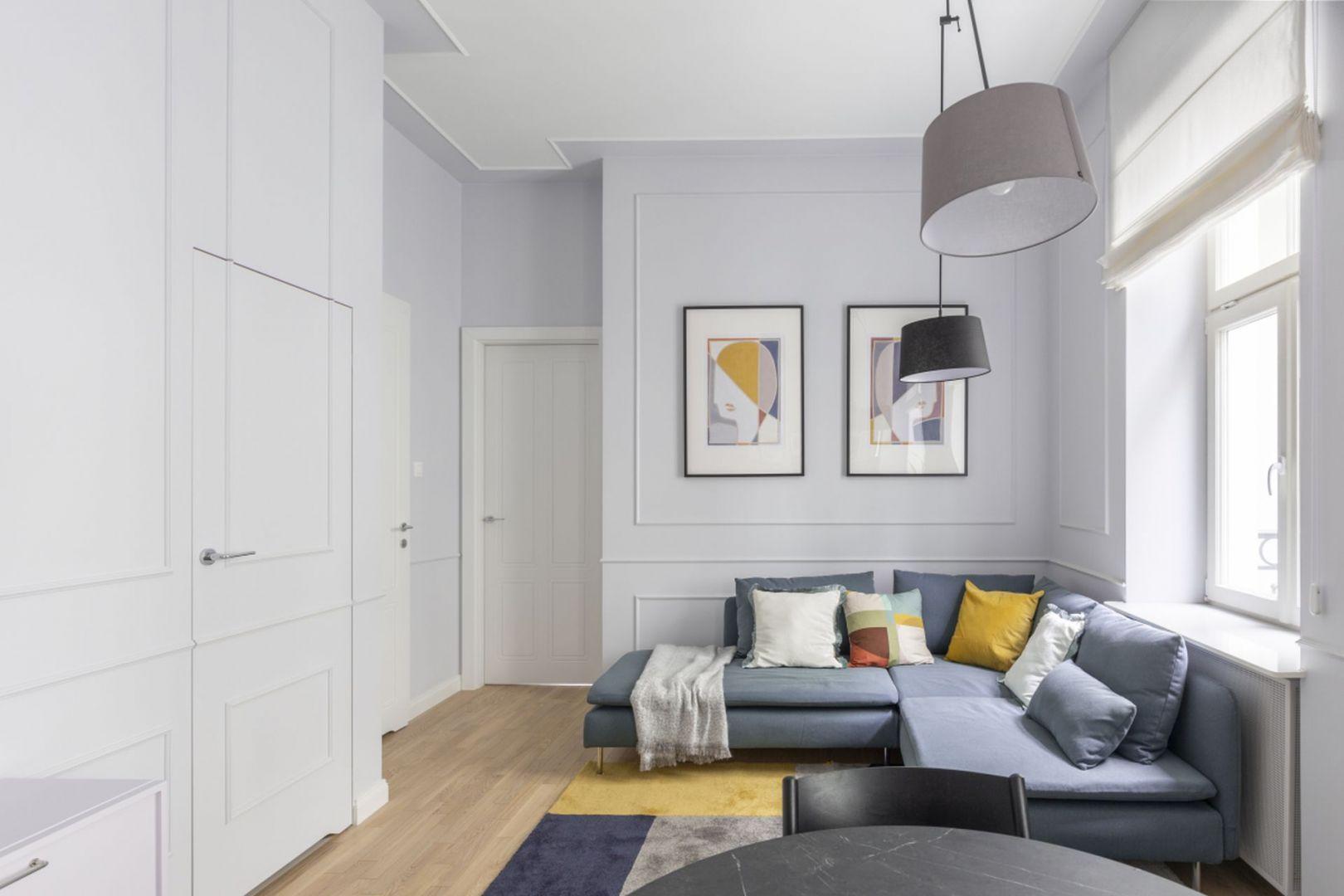 Mały salon w bloku ze sztukaterią na ścianie oraz z dębową podłogą. Projekt: Decoroom. Fot. Pion Poziom
