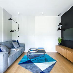 Mały salon w bloku, w którym mocnym elementem jest czarna ściana za telewizorem. Projekt: Sandra Maculewicz. Fot. Łukasz Pepol