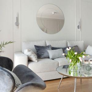 Nad sofą zawisło okrągłe lustro, które nawiązuje do stolika kawowego z okrągłym lustrzanym blatem. Projekt: Studio Projektowania Miśkiewicz Design. Fot. Anna Powałowska