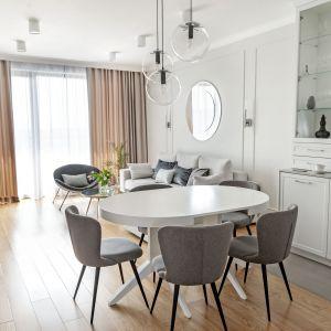 Jasnoszare ściany, białe meble i drewniana podłoga podkreślają spójność wystroju części dziennej. Projekt: Studio Projektowania Miśkiewicz Design. Fot. Anna Powałowska