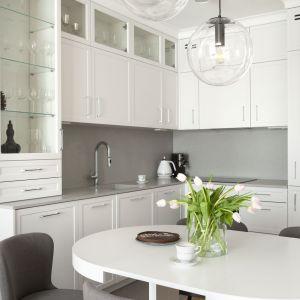 Powierzchnia frontów mebli w kuchni i ścian w salonie tworzy harmonijną całość. Projekt: Studio Projektowania Miśkiewicz Design. Fot. Anna Powałowska