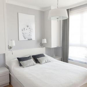Sypialnia została urządzona w bieli i szarości. Projekt: Studio Projektowania Miśkiewicz Design. Fot. Anna Powałowska