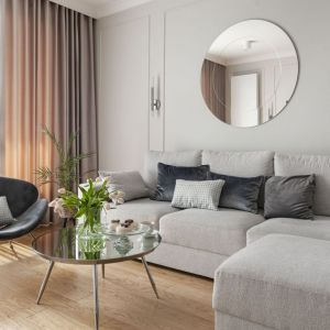 Fotel w salonie ustawiono przy wygodnej, trzyosobowej sofie zrobionej na zamówienie (Rafek Meble). Projekt: Studio Projektowania Miśkiewicz Design. Fot. Anna Powałowska