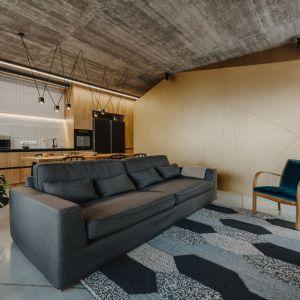 Nowoczesny, nieduży fotel w niebieskim kolorze w salonie. Projekt: Mili Młodzi Ludzie. Fot. Oni Studio