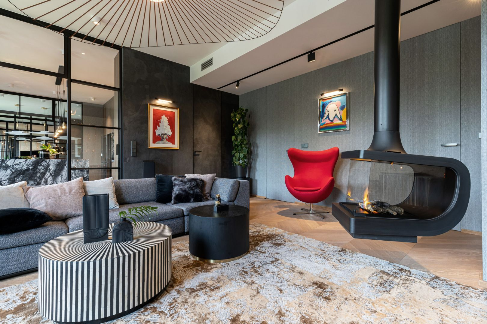 Czerwony fotel to odważny akcent w salonie urządzonym w ciepłej, złoto-brązowej kolorystyce. Projekt: Dorota Kwiecień, Gabriela Gajek Zakolska. Fot. Karol Kleszyk