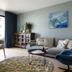 Niebieski fotel świetnie pasuje do szarej sofy w salonie. Projekt: Magdalena Bielicka, Maria Zrzelska-Pawlak, pracownia Magma. Fot. Kroniki Studio