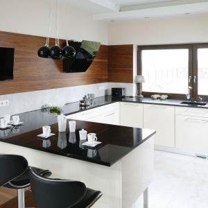 Nowoczesny okap kominkowy świetnie się prezentuje w tej przestronnej białej kuchni. Projekt Piotr Stanisz. Fot. Bartosz Jarosz