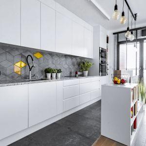 Mała kuchnia w bloku w białym kolorze z dodatkiem szarości. Szafki do sufitu zapewniają sporo miejsca na przechowywanie. Projekt: Łukasz Lenczewski, pracownia Tlen Architektura/ADC. Fot. Michał Plotzke