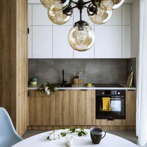 Mała kuchnia w bloku to połączenie bieli i drewna. Projekt: Poco Design. Fot. Yassen Hristov