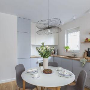 Mała kuchnia w bloku połączona jest z jadalnią. Urządzono ją w jasnych kolorach. Projekt: Decoroom Pracownia Architektury. Fot. Marta Behling, Pion Poziom – fotografia wnętrz