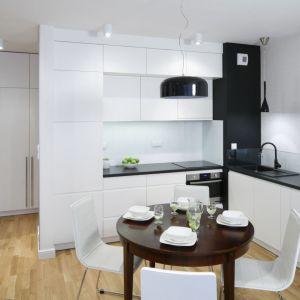 W tej niewielkiej kuchni dominuje biel - uniwersalna barwa, powiększająca optycznie wnętrze. Szafki wiszące sięgają do samego sufitu. Projekt: Ewa Para. Fot. Bartosz Jarosz