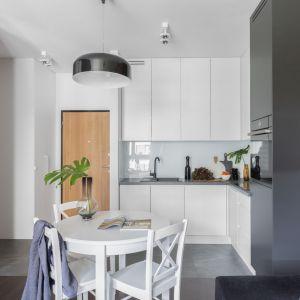 Mały aneks kuchenny połączony z jadalnią oraz z salonem. Szafki do sufitu zapewniają dużo miejsca na przechowywanie. Projekt: Emilia Rusińska, Decoroom