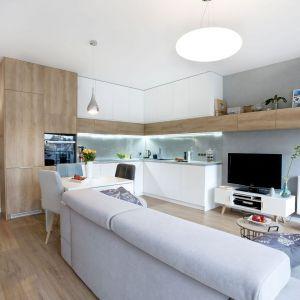 Biała zabudowa kuchenna pasuje do aranżacji małej salonu. Projekt i zdjęcia: Joanna Nawrocka