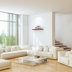 Ściany w jasnym, przestronnym salonie pomalowano na kolor biały. Fot. Baumit