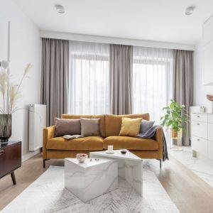 Ściany w salonie wykończono farbą w białym kolorze. Jasną aranżację ożywa kanapa w ciepłym, miodowym kolorze. Projekt: Katarzyna Szostakowska, Kate&Co. Fot. Marta Behling z PionPoziom