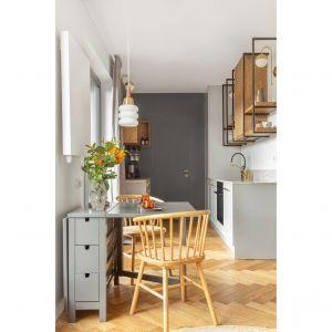 Uwzględniając nietypowe, wydłużone proporcje, strefa kuchni została oddzielona od pozostałej części kolorem ściany. Projekt:  Patrycja Morawska. Fot. Anna Laskowska/Dekorialove