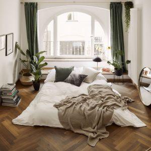 Ładna sypialnia w wakacyjnym stylu. Beżowe tapicerowane łóżko, piękne dekoracje i dużo roślin. Fot. WestwingNow