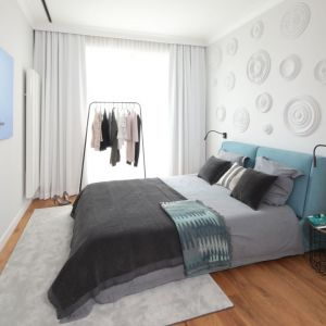 Ściana za łóżkiem w sypialni wykończona jest sztukaterią, a sama sypialnia utrzymana w chłodnej kolorystyce. Projekt Katarzyna Mikulska-Sękalska. Fot. Bartosz Jarosz