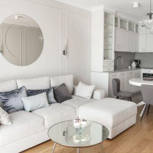 Ściana za kanapa w salonie wykończona jest listwami sztukateryjnymi, dzięki czemu przypominają słynną angielską boazerię. Projekt: Studio Projektowania Miśkiewicz Design. Fot. Anna Powałowska