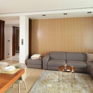 Ściana za kanapa w salonie wykończona jest fornirem z orzecha amerykańskiego. Projekt: Laura Sulzik. Fot. Bartosz Jarosz