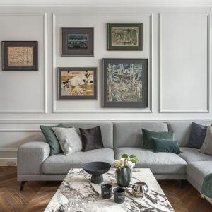 Ściana za kanapa w salonie wykończona jest sztukaterią w szarym kolorze. Na jej tle pięknie prezentują się obrazy. Projekt: Dawid Przewoźny, pracownia Whitecastle.pl. Fot. Tom Kurek