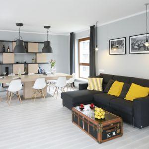 Ściana za kanapa w salonie wykończona jest szarą farbą w jasny kolorze. Na jej tle fajnie prezentują się dwie biało-czarne grafiki. Projekt: Maciejka Peszyńska-Drews. Fot. Bartosz Jarosz